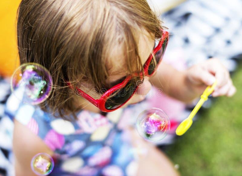 Маленькая девочка наслаждаясь дующ пузыри мыла стоковые фотографии rf