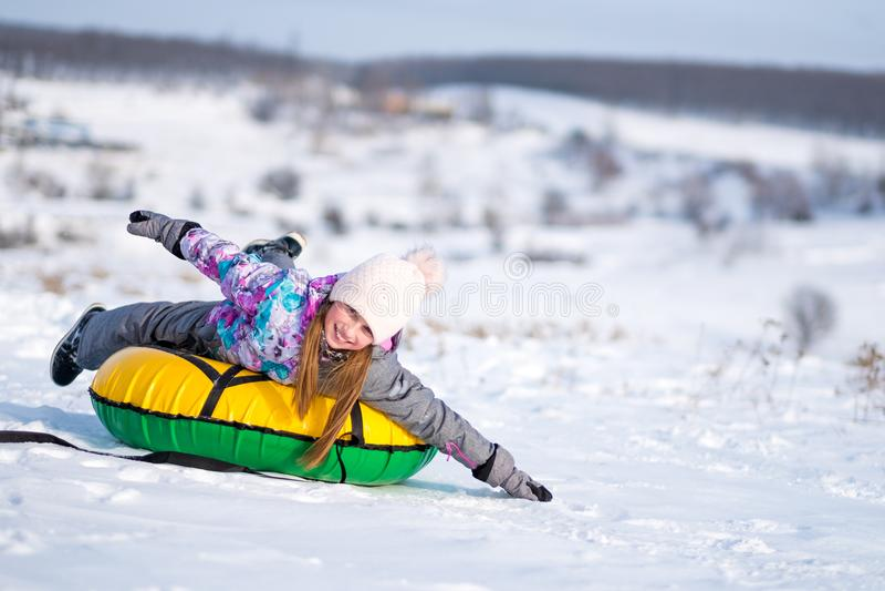 Маленькая девочка наслаждаясь трубопроводом снега на солнечной погоде стоковое изображение
