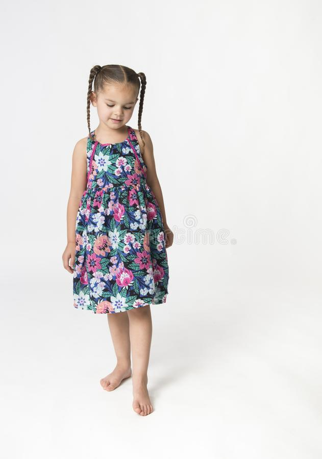Маленькая девочка на белой предпосылке смотря вниз стоковые фото