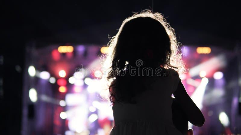 Маленькая девочка на ее плече ` s отца наблюдая и веселя в аудитории стоковая фотография rf