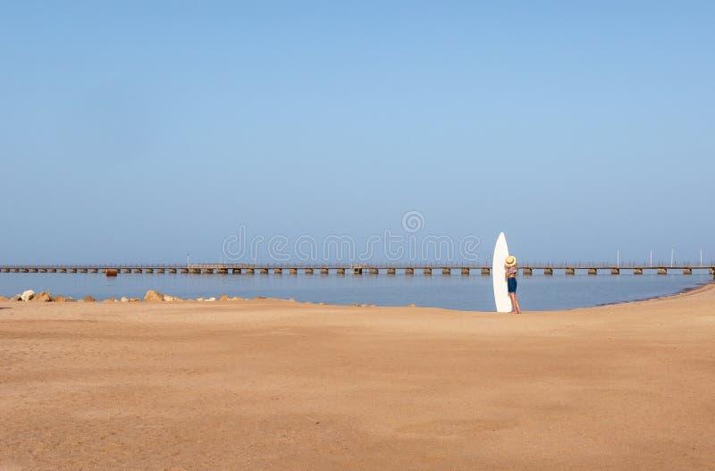 Маленькая девочка на пляже с surfboard, шляпа на предпосылке длинной пристани стоковое изображение