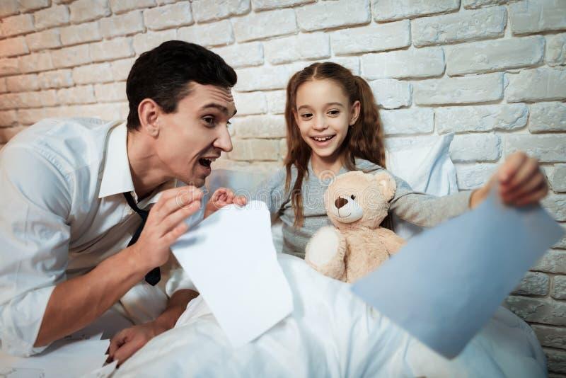 Маленькая девочка не позволяет ее отцу работать Маленькая дочь срывает вверх ее бумаги ` s отца стоковые фотографии rf