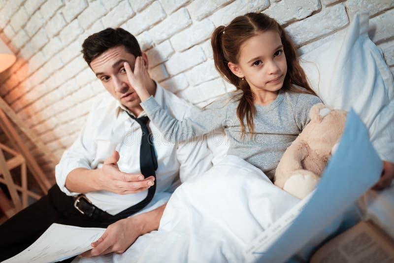 Маленькая девочка не позволяет ее отцу работать Дочь требует внимания занятого отца стоковое фото rf