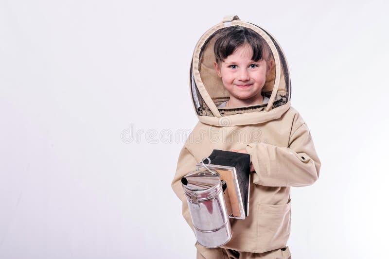 Маленькая девочка носит излишек определенный размер костюм пчелы в предпосылке белизны студии стоковые изображения
