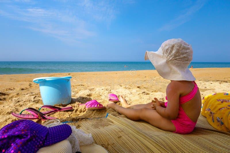 Маленькая девочка нося шляпу Панамы сидя в тени на песчаном пляже побережья Чёрного моря на курорте Anapa под голубым небом на со стоковое фото