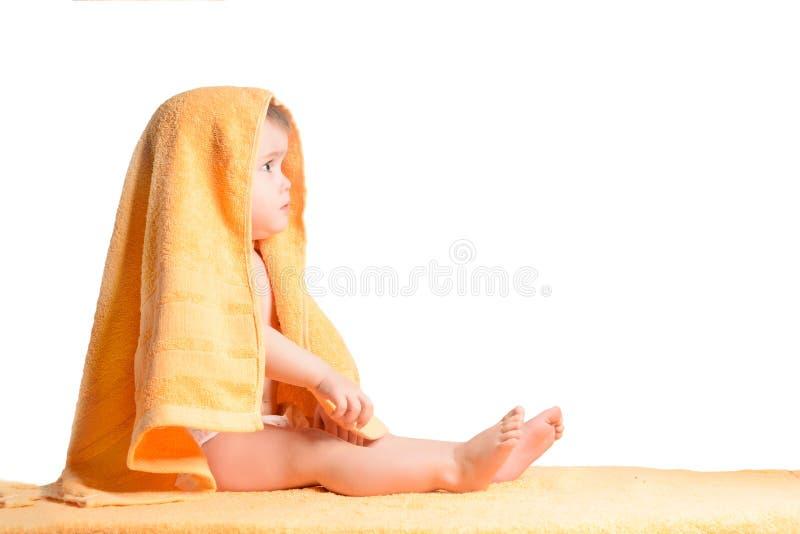 Маленькая девочка обернутая в желтом полотенце, на белой предпосылке стоковое изображение