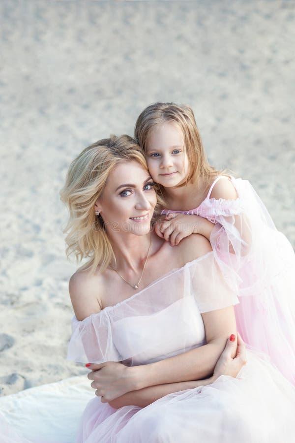 Маленькая девочка обнимает маму от задней части и улыбок Мать сидя на пляже с ее дочерью E Счастливая забота детства стоковое фото rf