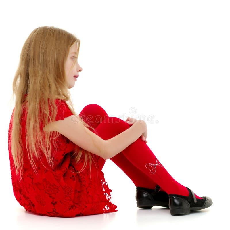 Маленькая девочка обнимая ее колени стоковое фото rf