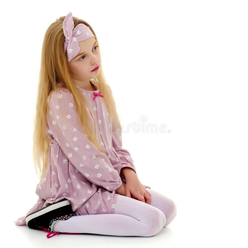 Маленькая девочка обнимая ее колени стоковое изображение rf