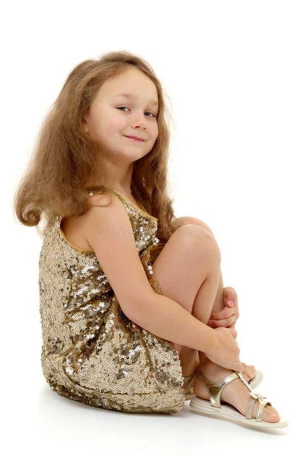 Маленькая девочка обнимая ее колени стоковая фотография rf