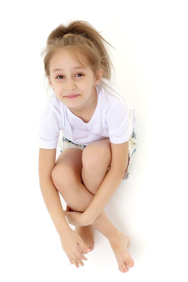 Маленькая девочка обнимая ее колени стоковые фото