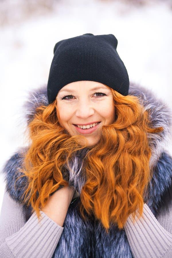 Маленькая девочка одетая в меховой шыбе на предпосылке зимы стоковые фото