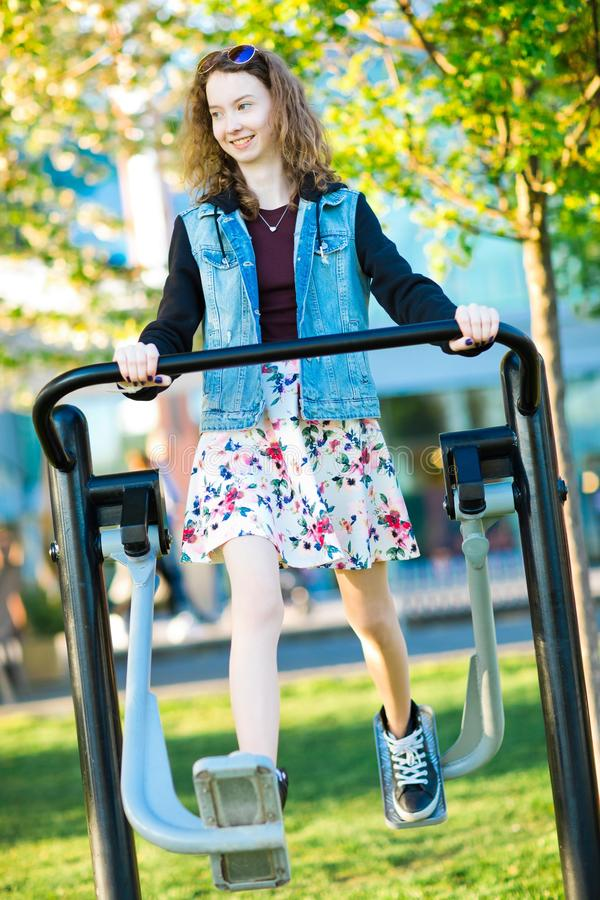 Маленькая девочка одетая в тренировке юбки бежать машина спортзала на открытом воздухе стоковая фотография