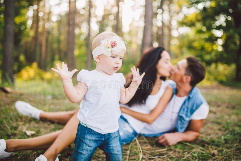 Маленькая девочка один год на предпосылке родителей отдыхая лежа на траве уча идти на природу в парке Первые шаги стоковые изображения rf