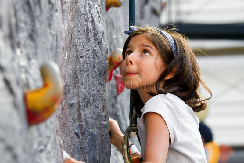 Маленькая девочка около для того чтобы взобраться стена утеса смотрит вверх с немного беспокойства стоковое фото rf