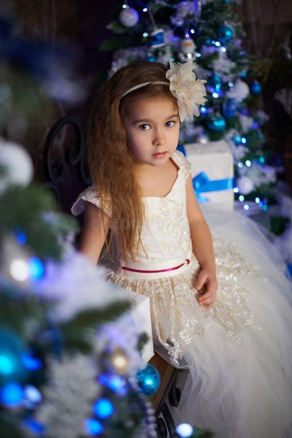 Маленькая девочка около 2 искусственных рождественских елок стоковая фотография rf