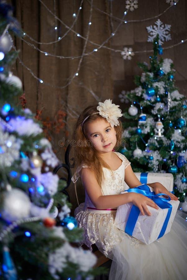 Маленькая девочка около 2 искусственных рождественских елок стоковое изображение rf