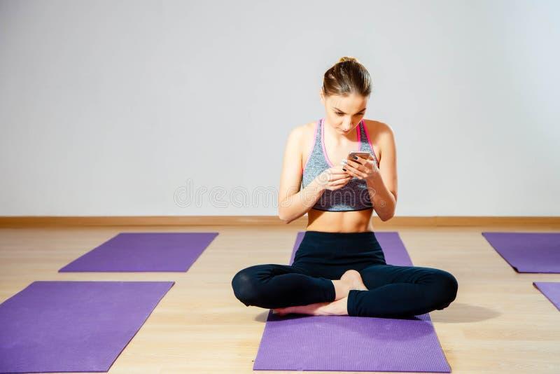 Маленькая девочка ослабляя после разминки Портрет красивой женщины спорт используя smartphone в спортзале стоковое изображение