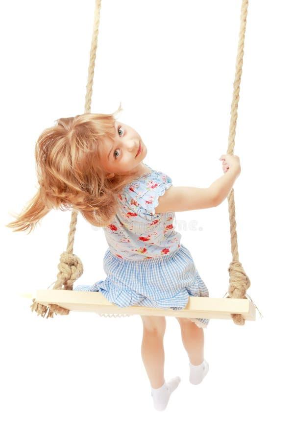 Маленькая девочка отбрасывая на качании стоковые фотографии rf