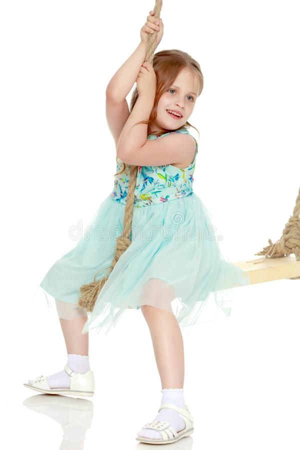 Маленькая девочка отбрасывая на качании стоковые фото