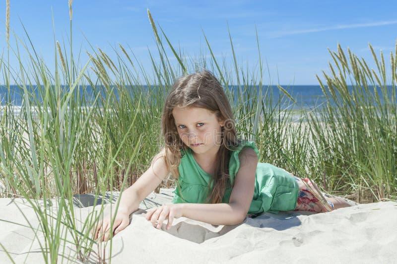 Маленькая девочка отдыхая на пляже стоковая фотография rf