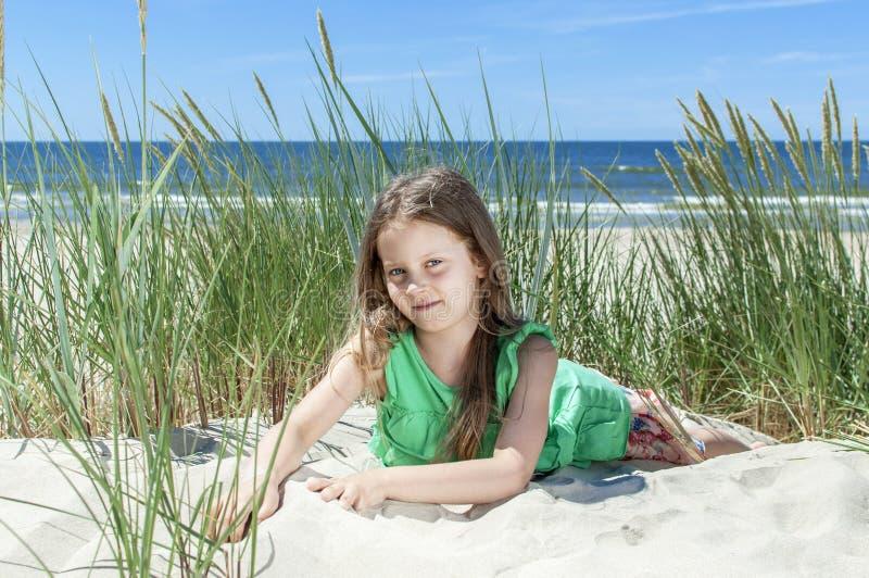 Маленькая девочка отдыхая на пляже стоковое изображение rf