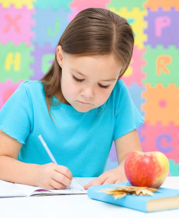 Маленькая девочка пишет используя пер стоковое фото rf