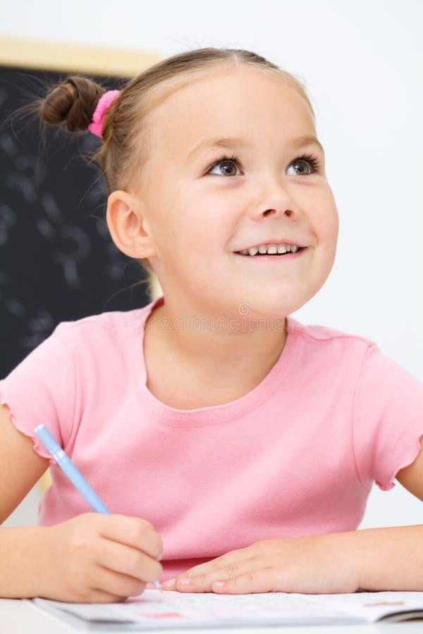 Маленькая девочка пишет используя пер стоковые фотографии rf