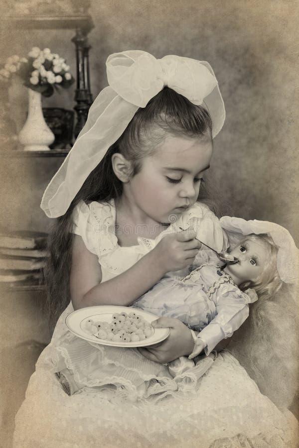 Маленькая девочка подает ее кукла стоковая фотография rf