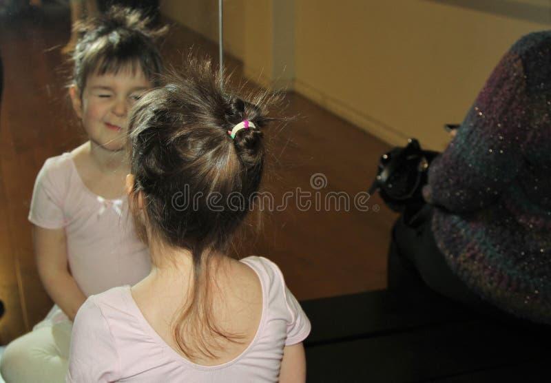 Маленькая девочка подмигивая перед зеркалом стоковое фото rf