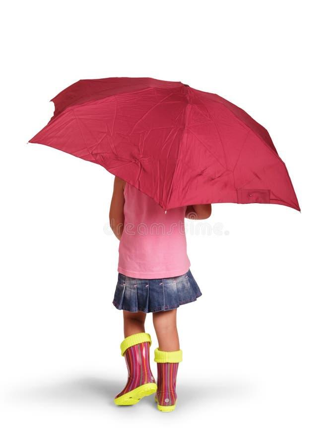 Маленькая девочка под зонтиком в резиновых ботинках, изолированных на белизне стоковые фото