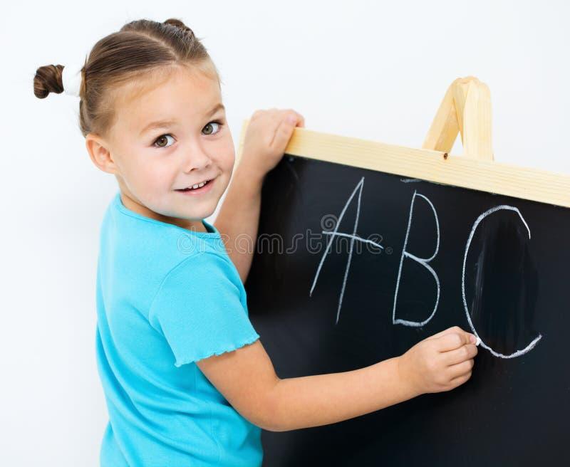 Маленькая девочка показывает письмо e на алфавите стоковое фото rf