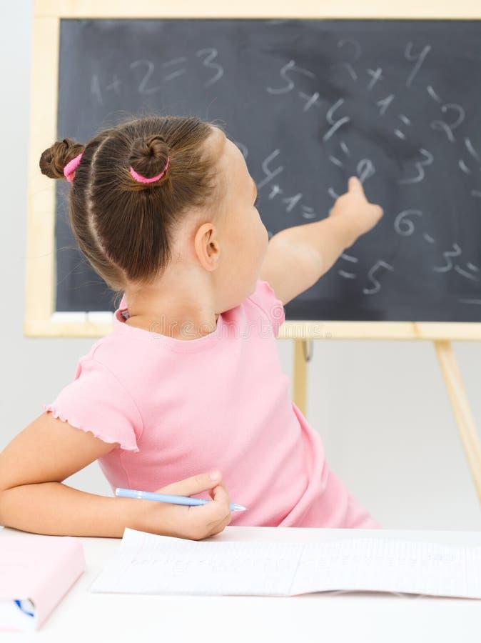 Маленькая девочка показывает что-то на классн классном стоковое изображение rf