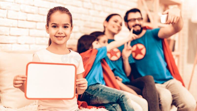 Маленькая девочка показывая пустую доску около милой семьи стоковые фото