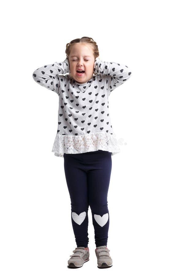 Маленькая девочка покрыла ее уши на предпосылке изолированной белизной стоковая фотография