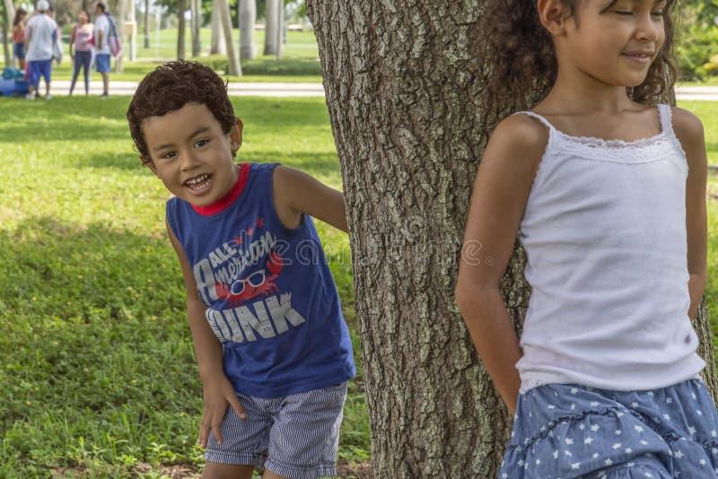 Маленькая девочка полагается с ее задней частью на дереве считая пока мальчик прячет за деревом стоковые фото