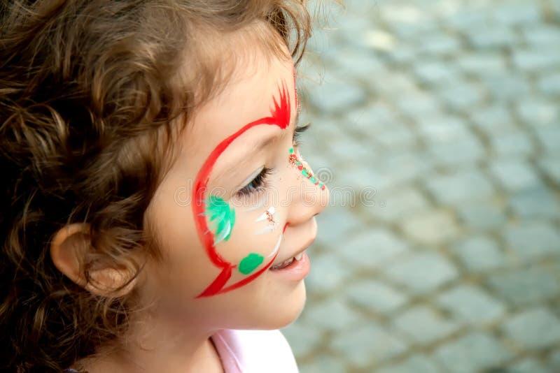 Маленькая девочка получая ее сторону покрашено стоковые изображения