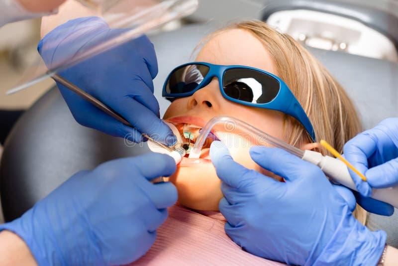 Маленькая девочка получая зубоврачебную процедуру в педиатрической зубоврачебной клинике стоковые изображения