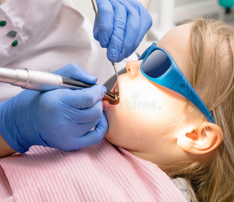 Маленькая девочка получая зубоврачебный порядок заправки в педиатрич стоковые фото