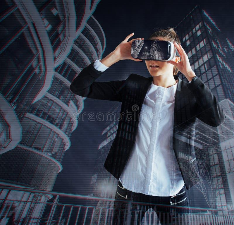 Маленькая девочка получая шлемофон опыта VR, использует увеличенные eyeglasses реальности, был в виртуальной реальности В городе  стоковое фото
