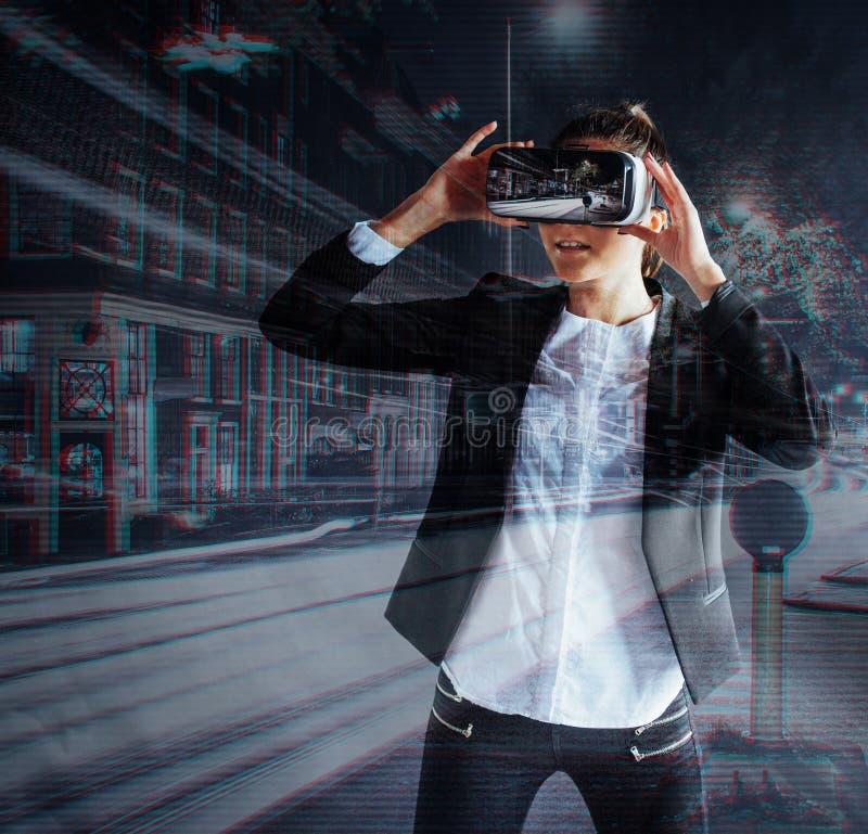 Маленькая девочка получая шлемофон опыта VR, использует увеличенные eyeglasses реальности, был в виртуальной реальности В городе  стоковое изображение