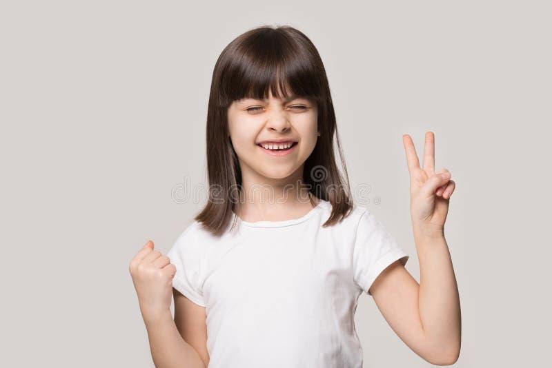 Маленькая девочка получила чему она хотела показывать символ жеста победы стоковое фото rf