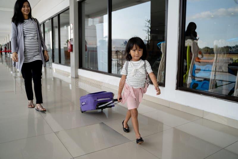 Маленькая девочка пошла с ее матерью пока вытягивающ чемодан стоковое изображение rf