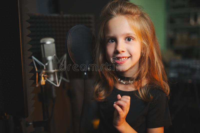 Маленькая девочка поя в студии звукозаписи стоковая фотография rf