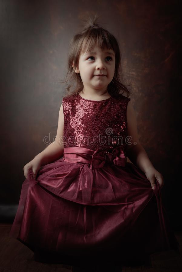 Маленькая девочка представляя в красном платье вечера стоковые фотографии rf