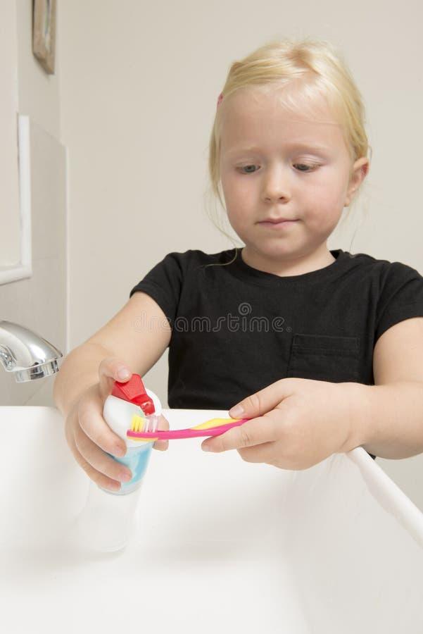 Маленькая девочка прикладывая зубную пасту на розовой зубной щетке в ванной комнате стоковая фотография rf