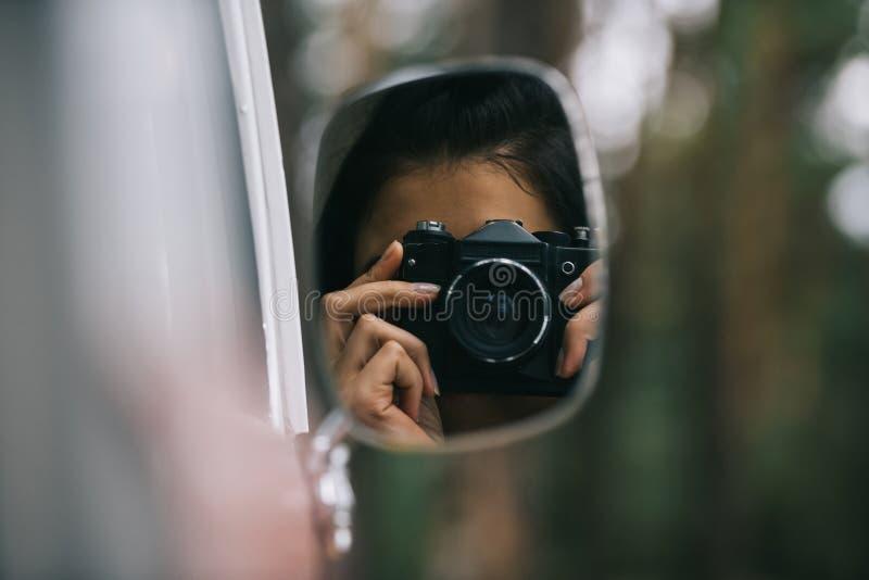 маленькая девочка принимая фото на камере через зеркало  стоковая фотография rf