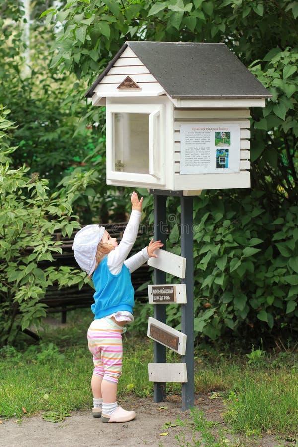 Маленькая девочка пробуя получить книгу из библиотеки улицы общины общественной BookCrossing стоковая фотография rf