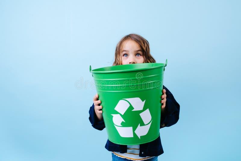 Маленькая девочка рассматривая зеленый ящик recicle Удержание в руках стоковые изображения