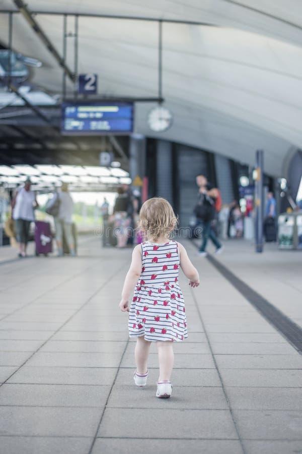 Маленькая девочка ребенок юрко идет вдоль толпить perron к стоковые изображения rf